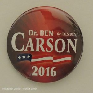 Red Dr. Ben Carson for President campaign button with white lettering and flag banner