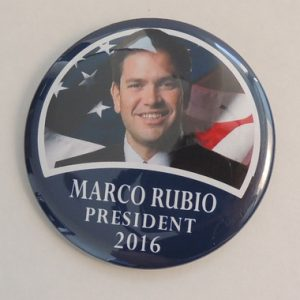 Marco Rubio for President 2016 blue campaign button.  Front face photo with flag background